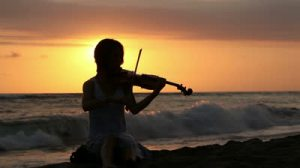 stock-footage-silhouette-of-woman-playing-romantic-music-on-violin-on-shore